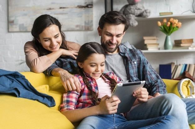 Un niño ve una tableta con sus padres.