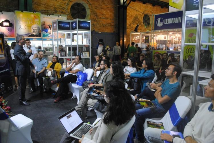 personas sentadas viendo al expositor durante la Feria del Libro junto a los stands