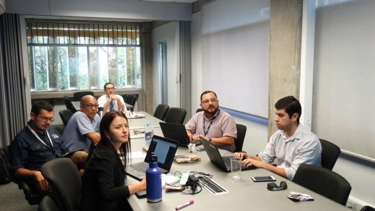 Cinco hombres y una mujer observando una presentación en una mesa de sesiones.
