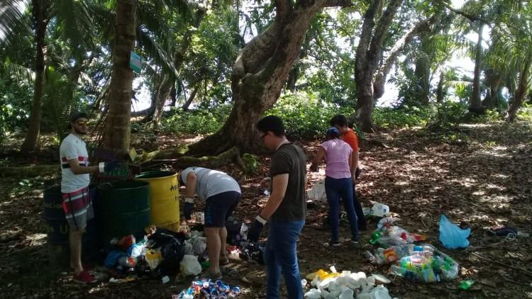 jóvenes recogiendo basura en una isla