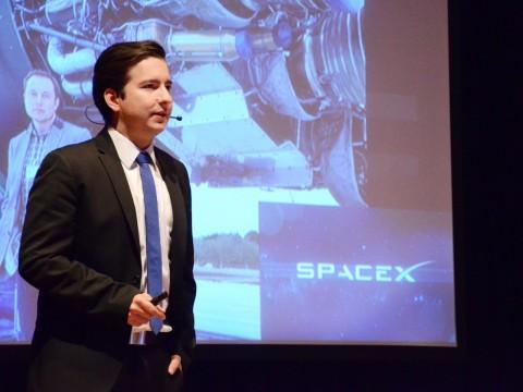 Marco Gómez en el escenario, frente a una proyección que dice SpaceX.