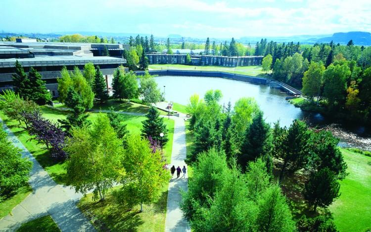 campus universitario con lago y árboles al fondo