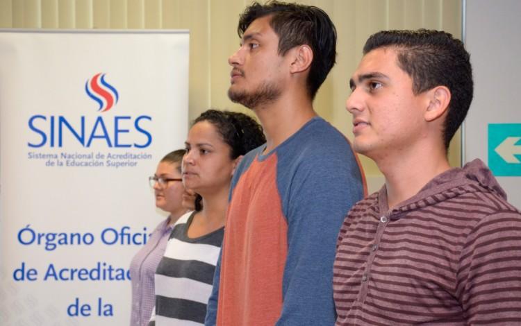 Estudiantes posando a la par de banner con logo de SINAES.