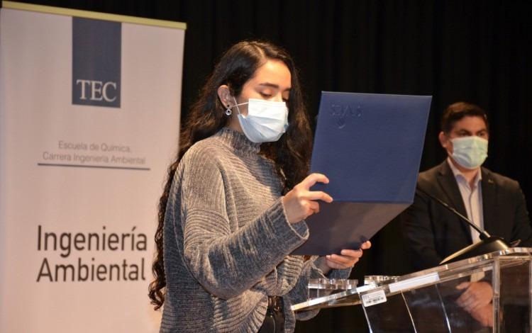 Estudiante sostiene y lee el certificado de acreditación.