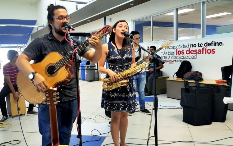 Un estudiante con guitarra y una estudiante cantando.