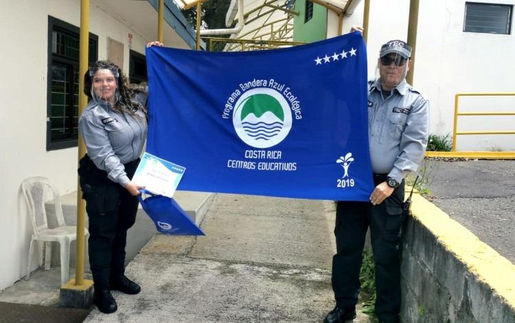 Dos guardas muestran la bandera azul del galardón.