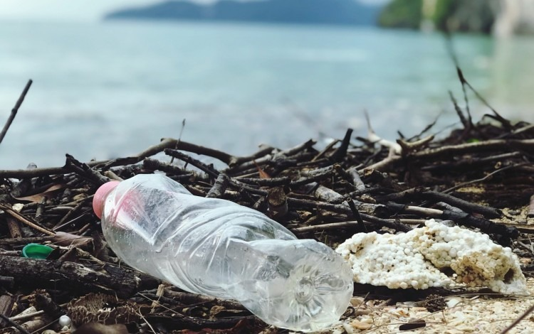 botella plástica y basura frente a playa