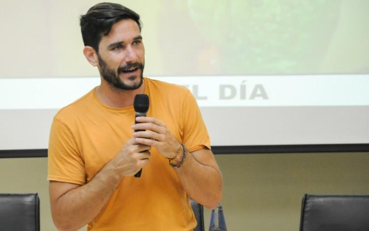 Hombre con un micrófono frente a muchos estudiantes dando una charla.