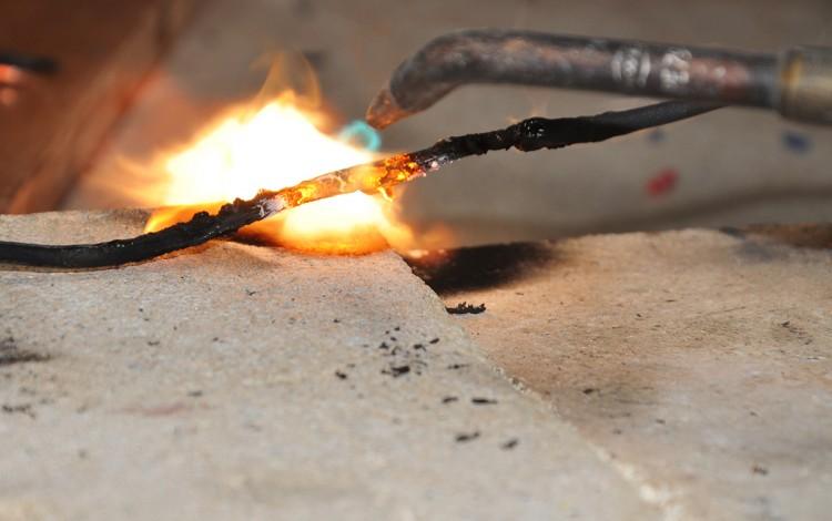 Un cable es sometido al fuego del soplete.