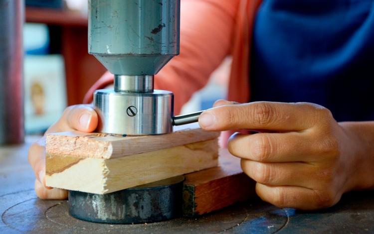 Mano de hombre cortando madera.
