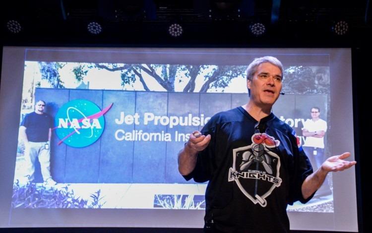 Bruce Callow frente a una proyección de una foto de un laboratorio de NASA.