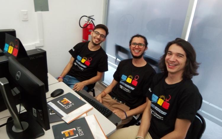 jovenes_programadores_sonriendo_sentados_frente_a_computadora_durante_competencia_