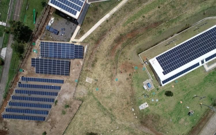 Vista aérea de los paneles solares, tanto en piso como en el tejado de un edificio.