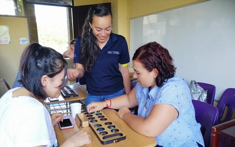 Imagen de una estudiante del TEC, una mamá y su hija aprendiendo matemática por medio de juegos.