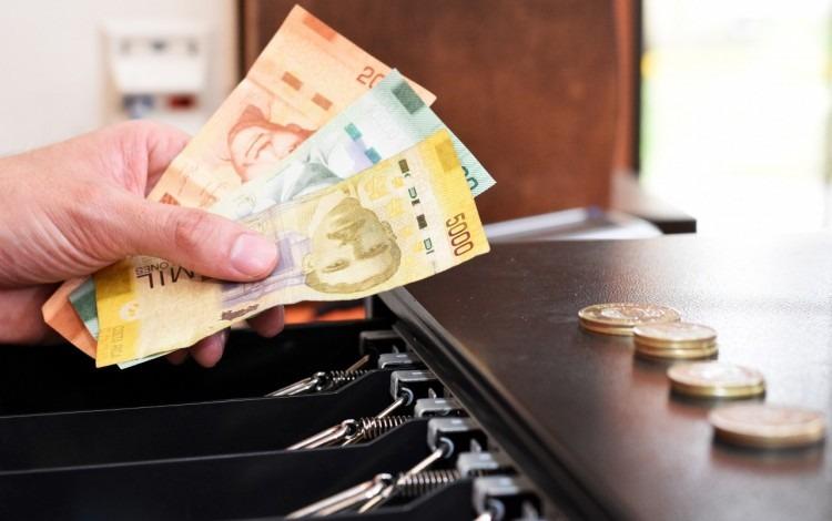 caja registradora abierta con monedas y persona con monedas en la mano