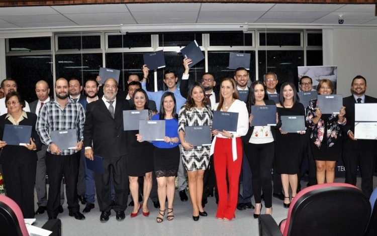 Los graduandos enseñan sus títulos.