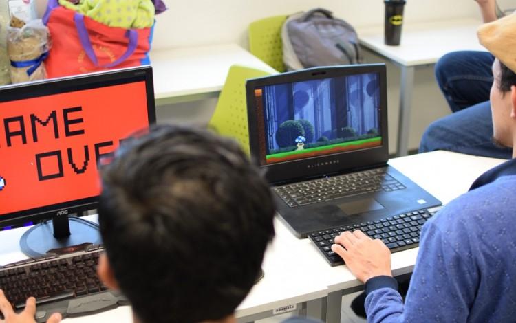 personas jugando videojuegos frente a una computadora
