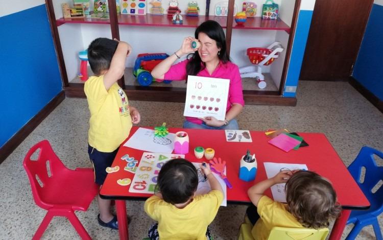 niños en una mesa compartiendo con la maestra en un aula
