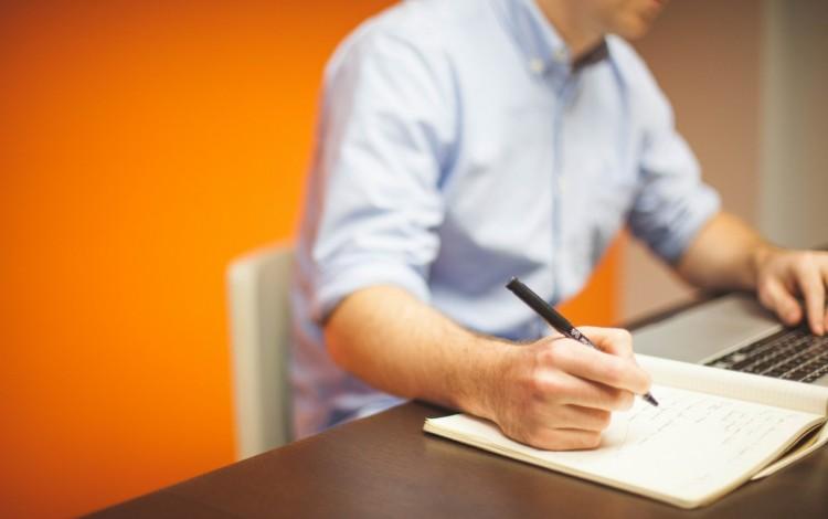 persona con lapiz en mano y computadora