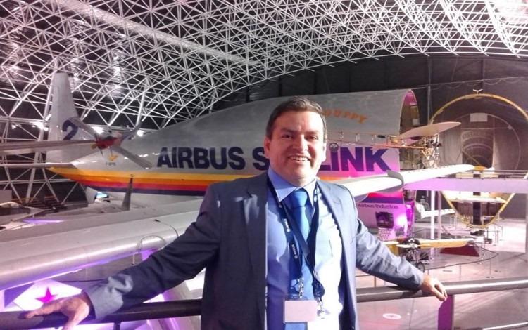 Victor Julio Hernández de pie con un avión estacionado detrás de él.