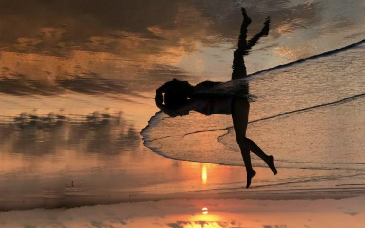 Reflejo de una mujer en la playa