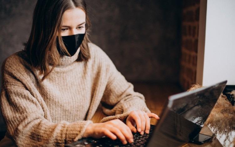 mujer con barbijo frente a computadora