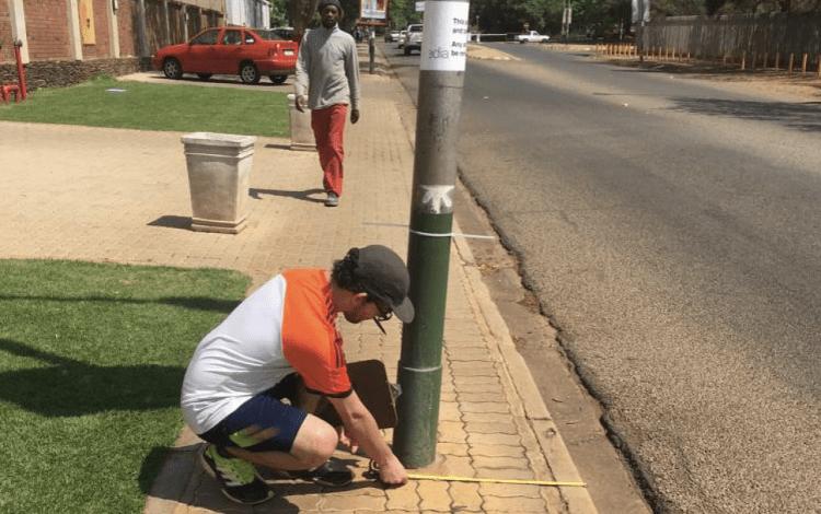 Joven tomando mediciones de obstáculos peatonales en Sudáfrica