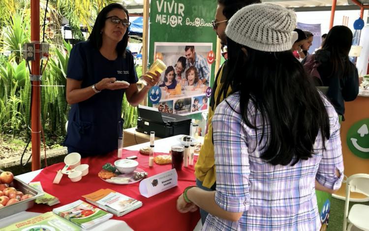 imagen de una mujer mostrando productos saludables a los estudiantes del TEC.