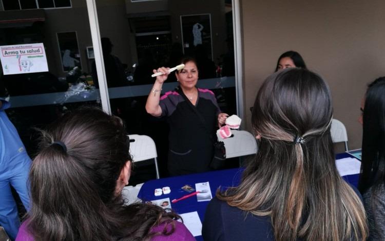 Imagen de una mujer mostrando a los estudiantes de la Sede Interuniversitaria de Alajuela, como se deben de lavar los dientes correctamente.