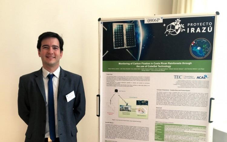 Marco Gómez junto al póster sobre el satélite tico.
