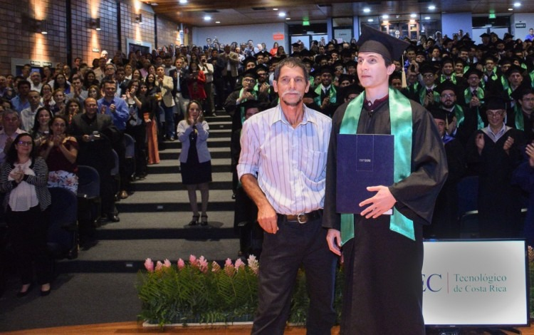 Joven graduado David junto  con su padre y detrás el auditorio con el resto de graduados
