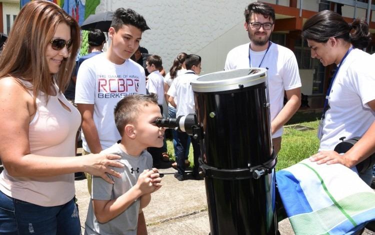 niño viendo a través de telescopio