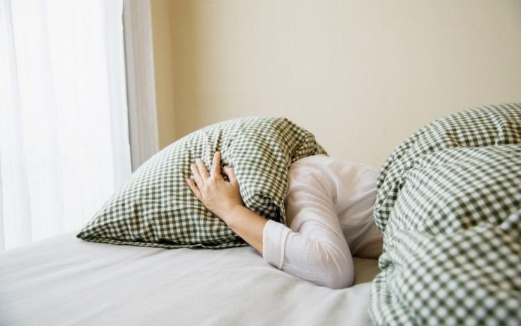 imagen de una mujer con su cabeza bajo la almohada.