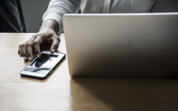 Una mujer en la computadora y usando el teléfono.