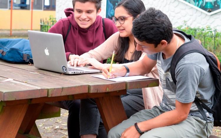 estudiantes frente a computadora en banca del pretil