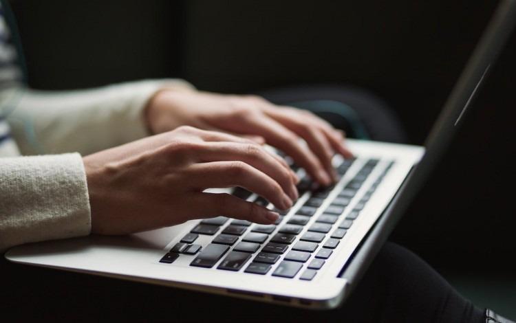 La imagen muestra las manos de una personas tecleando una computadora