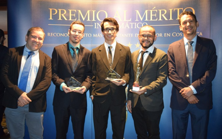 Los cinco ingenieros posan frente a un rótulo de Premio al Mérito Informático.