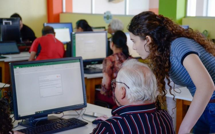 Adulto mayor en computadora asistido por una mujer estudiante.