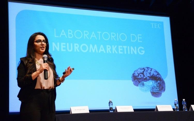 Mujer exponiendo el tema de neuromarketing a un grupo de empresarios.