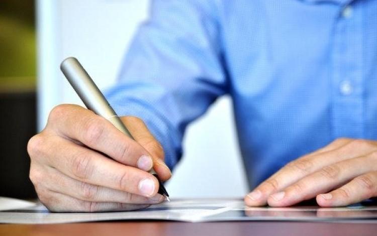 hombre escribiendo con un lapicero