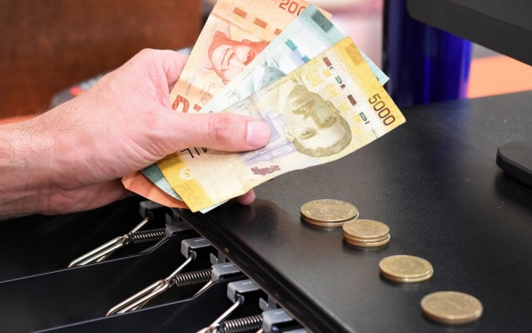 mano con billetes y monedas al lado