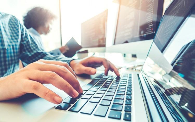 manos de persona en teclado desarrollando software