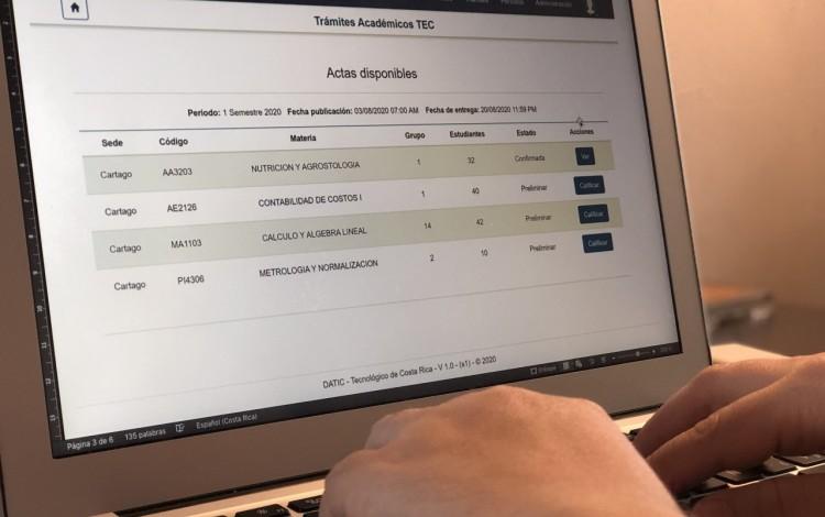 mano en computadora con sistema de actas