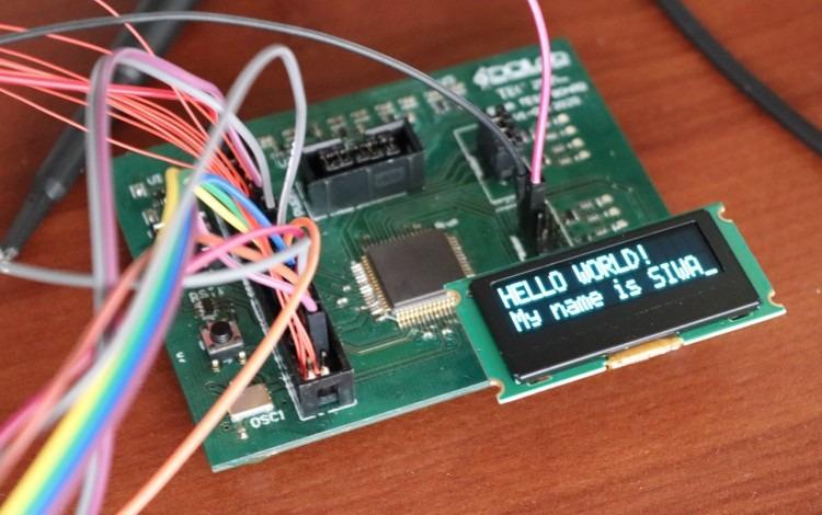 Tarjeta de circuitos, con cables y una pantalla que dice Hello World, My name is SIWA
