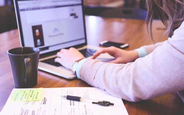 Uma mujer trabajando en una computadora portátil.