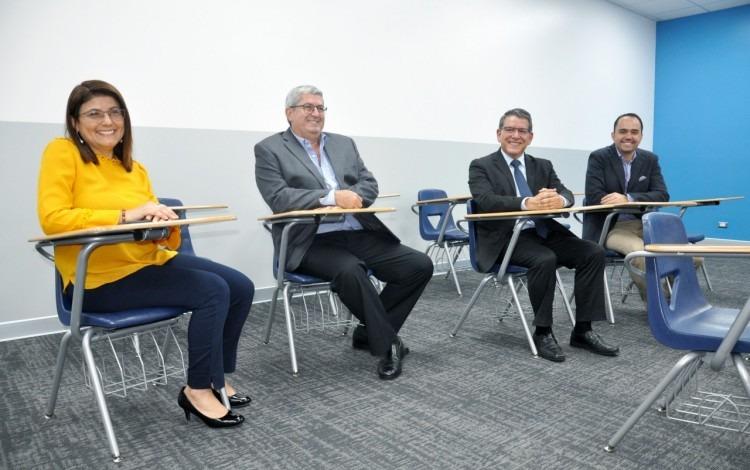 Las cuatro personas sonríen sentadas en pupitres.