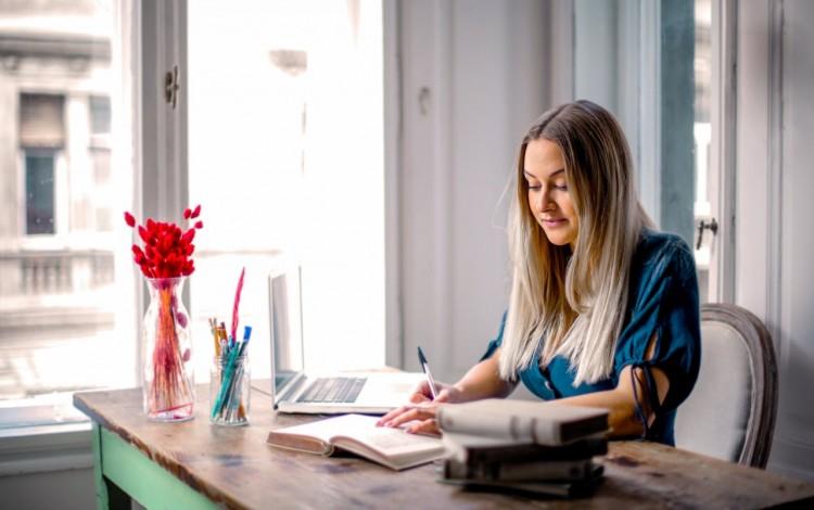 Mujer trabajando en computadora portátil en escritorio dentro de una casa.