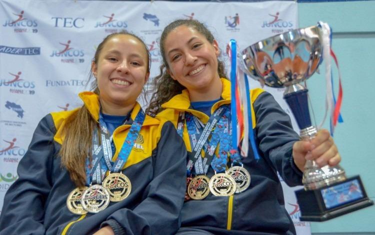 Dos jugadoras posan con el trofeo y las medallas.