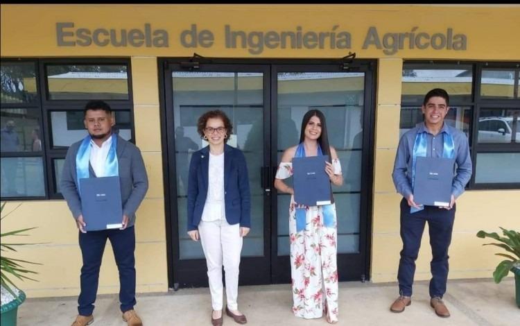 Imagen de una profesora y tres estudiantes mostrando su título universitario.