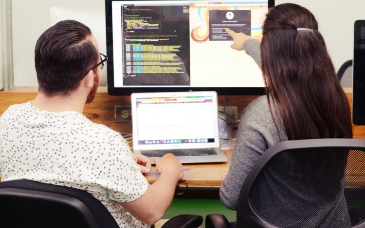 jóvenes señalando una computadora